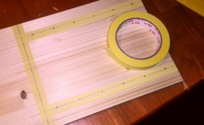 Wooden cutting boards rack / holder prepared for boring holes with paint masking tape
